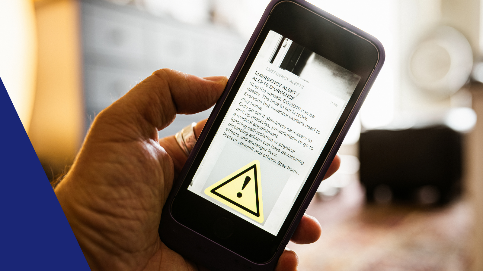 A cell phone in someone's hand with an emergency alert open on the screen